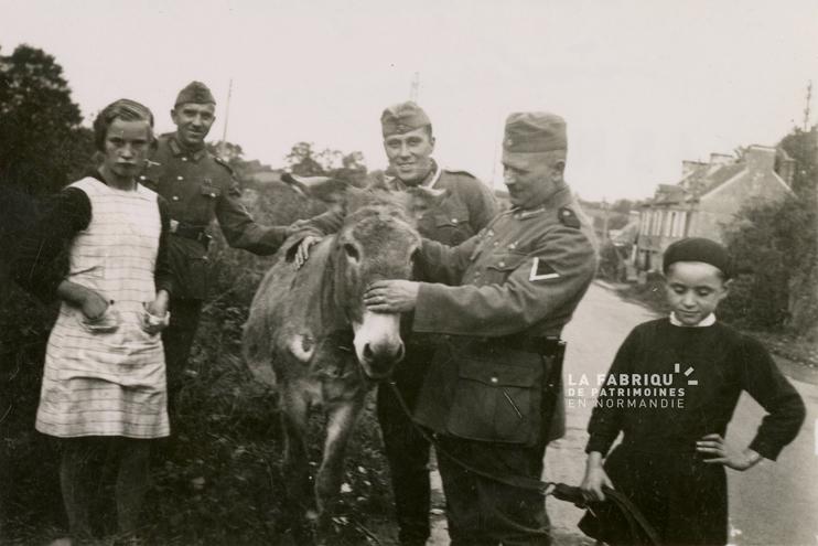 Deux enfants et leur âne, en compagnie de soldats allemands pendant l`Occupation  ( Fonds Pottier/La Fabrique de patrimoines en Normandie).