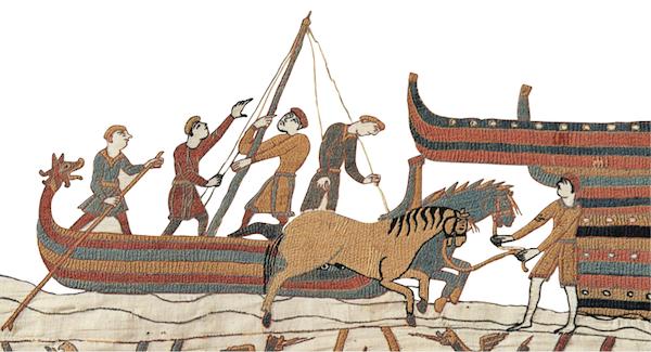 La flotte normande débarque à Pevensey, les navires sont à clins, de type scandinave, les chevaux sont débarqués (ces navires pouvaient aussi transporter du bétail) et les figures de proue et de poupe sont enlevées en arrivant sur le rivage (Avec l'aimable autorisation de la Ville de Bayeux).