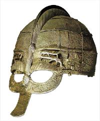 """On a retrouvé dans des tertres princiers du sud de la Suède, à Vendel et Valsgärde, datés vers le VIIe siècle, soit environ deux siècles seulement avant le début de l'ère des Vikings, un armement somptueux de princes locaux, belles épées ouvragées, garnitures de boucliers, mais aussi plusieurs casques décorés. Nous voyons ici un autre exemple que celui présenté en début d'article. La calotte est en fer recouvert de décoration et de feuilles de bronze. On y voit des scènes cultuelles, des processions de guerriers et un cavalier (qui pourrait être le dieu Odin sur son cheval). Ces casques pouvaient être garnis d'oreillères de fer ou d'une bavière de maille, comme nous l'avons vu précédemment, ce qui était le cas sur ce modèle où nous voyons les attaches de fixation. Ce modèle """"à lunettes"""", avec son nasal se répartissant pour protéger les yeux est un prédécesseur de ce que seront les casques ultérieurs du type de Gjermundbu. (Historiska Statens Museum Stockholm)."""