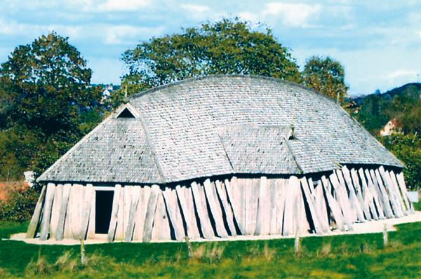 Maison reconstituée à Fyrkat, au Danemark, d'après les vestiges révélés par les fouilles archéologiques du camp de Fyrkat fondé vers 980 par le roi du Danemark, analogues aux vestiges retrouvés sur les autres camps, comme celui de Trelleborg. La rangée de poteaux extérieurs, de renfort, était inclinée. Les murs, en bois debout, étaient bombés et la toiture convexe, comme à Vorbasse, comme sur d'autres exemples du nord-ouest de l'Angleterre, sous l'influence danoise et comme en Normandie, à Mirville et à Boscherville, architecture danoise typique de cette époque. (© Heimdal).