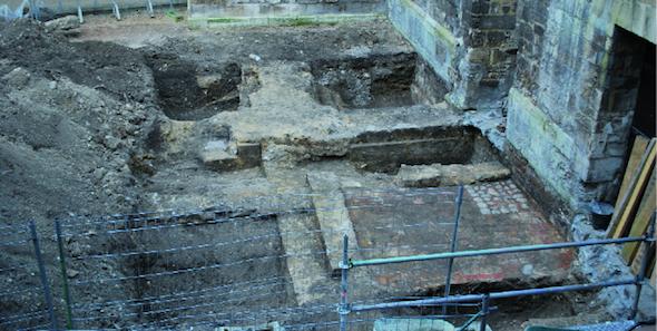Sondage archéologique dans la cour de la Maîtrise ; le bloc est en réemploi dans la maçonnerie au centre de la fouille ( D. Pitte).