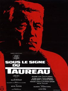 """Sous le Signe du Taureau, réalisé en 1969 avec Jean Gabin (Raynal), Suzanne Flon (Christine), Alfred Adam. Raynal, directeur d'une usine aéronautique vient d'achever un prototype de fusée qui explosera lors d'un essai. La faillite l'atteint, ses amis et sa famille l'abandonnent. Il part s'isoler en Normandie au bord du gouffre mais Christine, son épouse, viendra le retrouver et l'aidera à poursuivre ses recherches. Quelques scènes furent tournées dans le hall de la gare de Rouen et, les bureaux du journal local """"Paris Normandie"""". C'est à Deauville qu'il trouvera refuge (DR)."""
